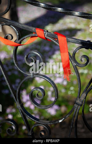 Red Ribbon on Fence - Stock Image