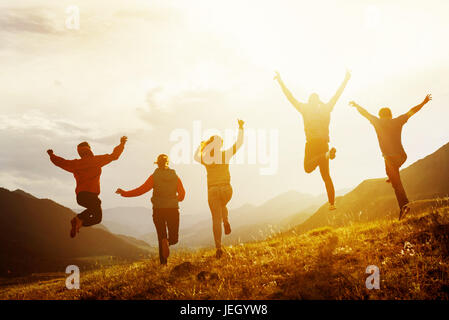 Group of happy friends run and jump - Stock Image