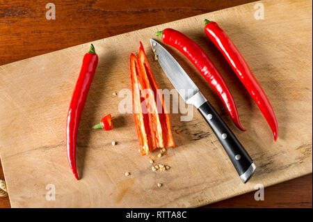 Deseeding Red hot chilli peppers on a carving board with knife - Stock Image