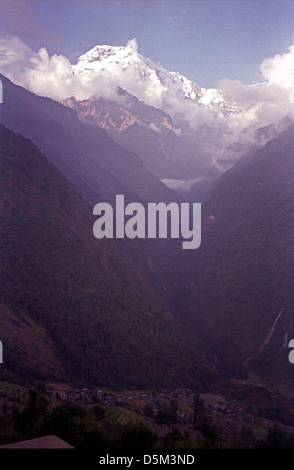Misty evening view of Modi Khola Valley from Chomrong on Annapurna circuit with snow peaks behind - Stock Image