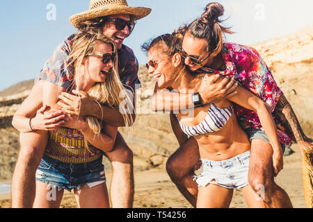Cheerful happy group of people friends laugh a lot outdoor at the beach - summer travel vacation concept with women carrying men - sun and funny lifes - Stock Image