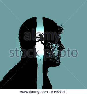 Man struggling to climb gap inside of man's profile - Stock Image