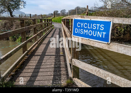 Cyclists Dismount sign notice on a footbridge over the River Sid at Fortescue, Sidmouth, Devon, UK - Stock Image