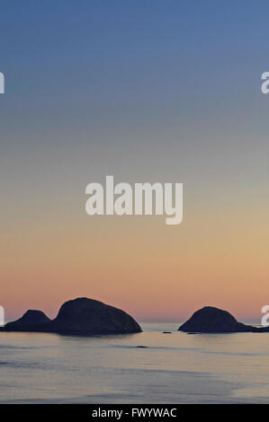 Two islands are silhouetted against the colorful sky at sunset in the North Atlantic. - Stock Image
