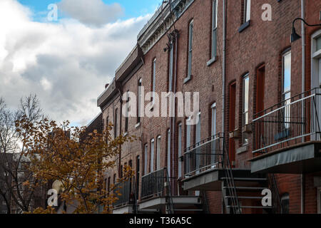 Facades of traditional North American residential buildings, red brick houses, taken in the center of Montreal, the second biggest city of Canada, and - Stock Image