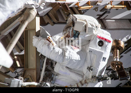 Expedition 59 NASA astronaut Anne McClain works on the power supply during a spacewalk outside the International Space Station March 22, 2019 in Earth Orbit. Astronauts McClain and Hague spent six-hours and 39-minutes outside the space station to upgrade the orbital complex's power storage capacity. - Stock Image