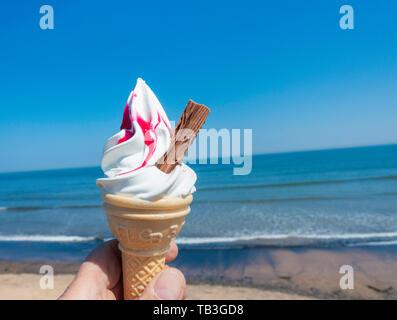 Ninety Nine ice cream cone with raspberry against blues sky and sea. UK - Stock Image