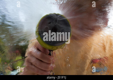 Child spraying water with a garden hose - Stock Image