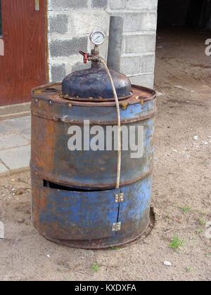 Homemade steem boiler from metal barrel outdoor - Stock Image