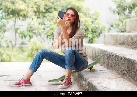Woman sitting on a skateboard on steps applying lipstick - Stock Image