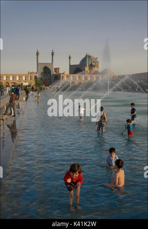 Kids playing int he public fountains and pool in Naqsh-e Jahan Square. Imam Square, Isfahan city, Iran - Stock Image