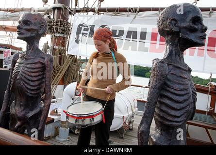 A G8 protester drumming between statues of starving Africans at the city port in Rostock, Germany, 1 June 2007. - Stock Image