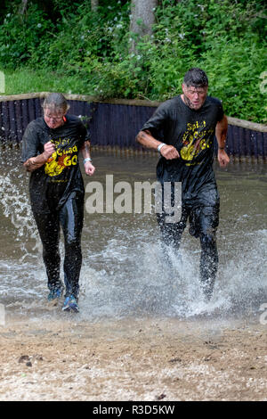 Rather soiled mud runners around a water crossing - Stock Image