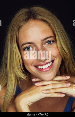 Young woman smiling with hands clasped under chin, portrait - Stock Image