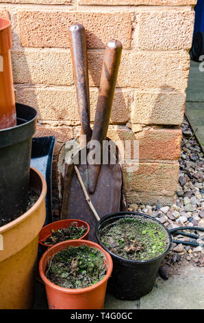 A couple of small hand shovels propped up against a house wall with some plant pots in a residential back garden. - Stock Image
