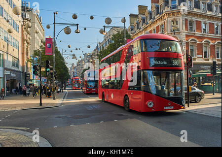 A red double decker bus in London's West End travels down Oxford Street. London buses are a great way to travel - Stock Image
