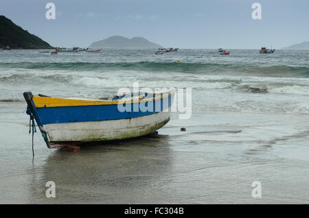 old wooden fishing boat on the beach at sunset - Stock Image