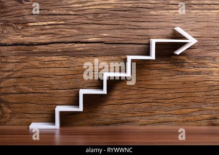 Close-up Of White Increasing Staircase Arrow On Wooden Background - Stock Image