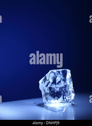 A large square cube / block of ice slowly melting. - Stock Image
