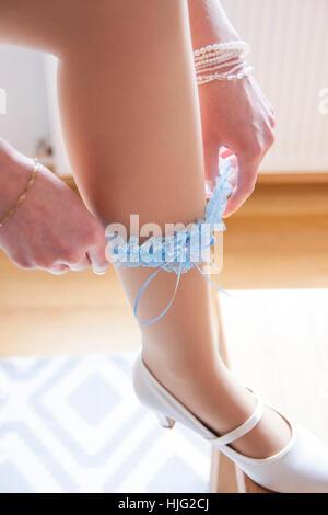 Bride,garter,blue,foot,woman,wedding,wedding day,shoe,brauhuh,white,pumps,hand,bracelet,burgundy,dress,Most beautiful,day,in,lif - Stock Image