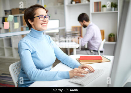 Cheerful employee in casual pullover sitting in fornt of computer, typing and laughing at something funny - Stock Image
