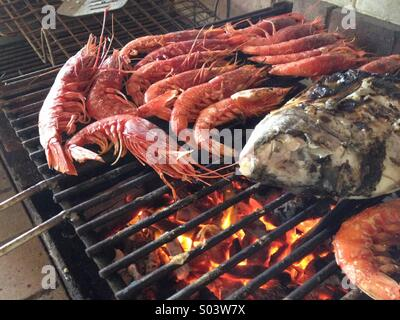 Cooking seafood on grill - Stock Image