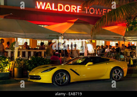 Bright yellow 2014 Chevy Corvette parked in front of the Room Mate Waldorf Towers on Deco Drive, Miami South Beach, - Stock Image