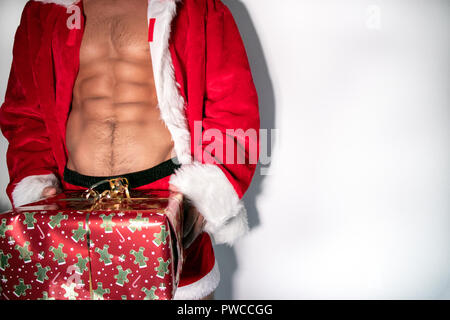 Sexy male santa with open jacket revealing six pack abs and fit body, wearing shorts, carrying a gift - Stock Image