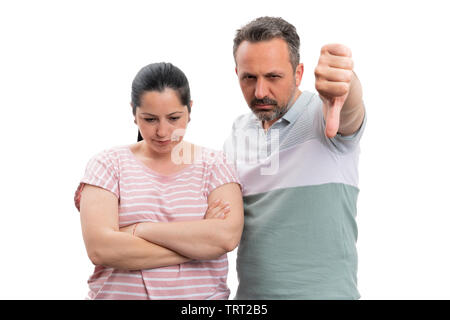 Man showing thumb-down as dislike gesture to upset woman with crossed arms isolated on white background - Stock Image