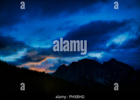 last color of sunset during the blue hour over the mountains of Alta Badia with cloudy sky, Dolomites - Italy - Stock Image