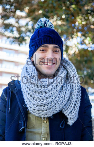 A young boy dressed in winter clothes and a wool hat smiles in an urban environment. - Stock Image