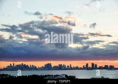 Miami Florida Biscayne Bay downtown city skyline high rise buildings clouds storm front sunset jet plane commercial airliner - Stock Image