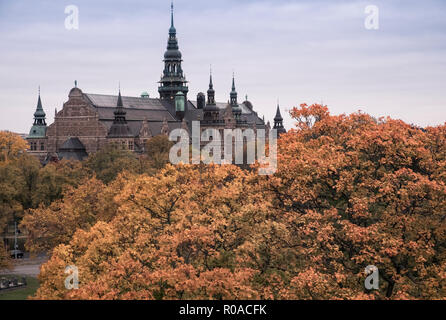 Exterior of Nordic Museum (Nordiska museet) on Djurgarden island, with autumn coloured trees in the foreground, Stockholm, Sweden - Stock Image