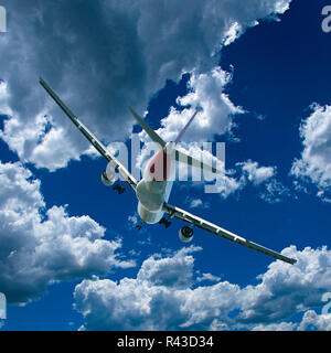 An artistic skyscape view of a commercial passenger jet aircraft flying in a vibrant blue sky, with bright white coloured Cumulus clouds. - Stock Image