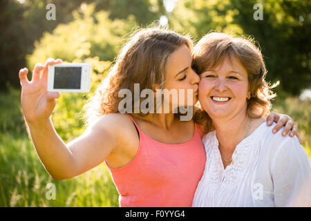 Adult daughter kissing her senior mother while taking selfie photo with mobile phone - Stock Image