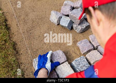 pavement construction - worker laying granite stone pavers - Stock Image