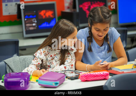 Junior high school girl students using smart phone at desk in classroom - Stock Image