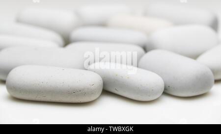 white smooth stones of elongated shape - Stock Image