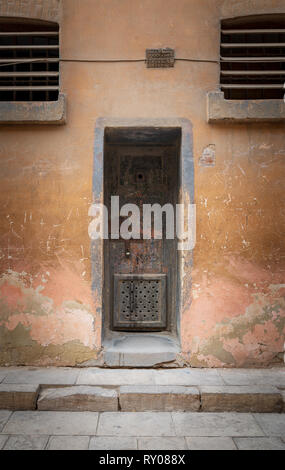 Closed rusted iron cell door and weathered grunge stone wall in closed abandoned prison at Cairo Citadel, Egypt - Stock Image