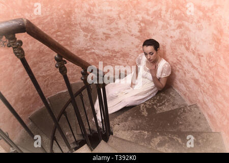 Beautiful young woman in authentic regency gown posing on spiral antique staircase - Stock Image