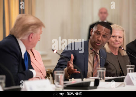 Johnny C. Taylor, Jr., president and CEO of the Society for Human Resource Management, right, speaks during the American Workforce Policy Advisory Board Meeting chaired by U.S President Donald Trump, left, in the State Dining Room of the White House March 6, 2019 in Washington, DC. - Stock Image