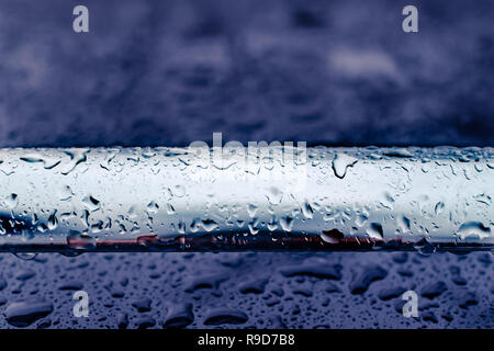 car roof railing abstract closeup after rain, dark mood, red reflection - Stock Image