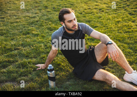 Image of a handsome young strong sports man posing outdoors at the nature park location resting sitting listening music with earphones. - Stock Image