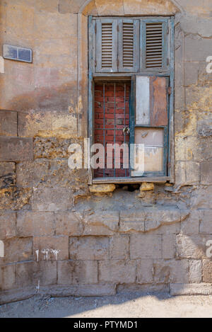 Broken windows and grunge stone bricks wall in abandoned Darb El Labana district, Cairo, Egypt - Stock Image