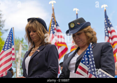 Merrick, New York, U.S. - May 26, 2014 - L-R, MARGARET BIEGELMAN and DEBRA BERNHARDT, members of the Merrick American Legion Auxiliary Post 1282, participate in The Merrick Memorial Day Parade and Ceremony. They bowed their heads during a Moment of Silence, for those who died in war while serving in the United States military. Credit:  Ann E Parry/Alamy Live News - Stock Image