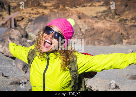 Young beautiful woman laugh and smile with joyful and open arms enjoying the alternative hiking vacation in outdoor mountains in summer - sunny day an - Stock Image