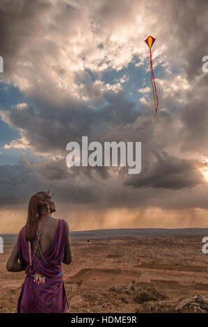 A Maasai Warrior Tribesman Flying a Kite in Traditional Tribal Dress. Kenya, Africa. Scenic View. Vertical format. - Stock Image