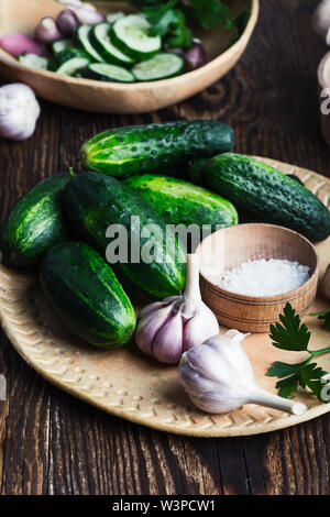Bowl of freshly picked organic cucumbers and garlic, fresh salad with homegrown vegetables and parsley on rustic  table, plant based food, close up, s - Stock Image