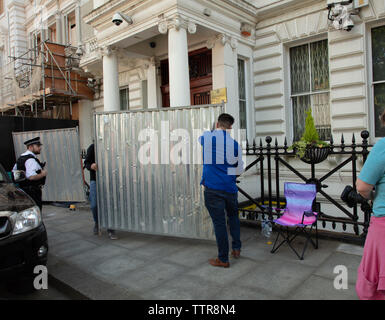 London, UK. 17th June 2019. Richard Ratcliffe on hunger strike in front of the Iranian embassy in London in protest of the detention of his wife Nazanin Zgahari in Iran over spying allegations. Embassy staff and builders start moving the large iron panels under the watchful eye of a police officer. Credit: Joe Kuis / Alamy - Stock Image