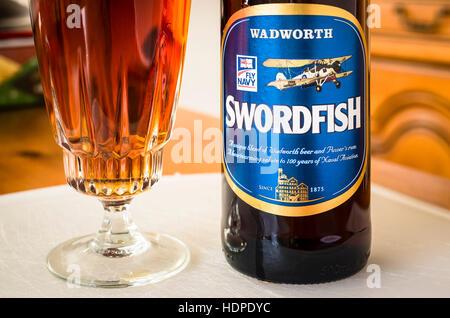 Glass of bottled Wadworth SWORDFISH beer brewwed in Wiltshire UK - Stock Image